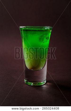 Green alcoholic shot glass with absent, irish cream, liquor on elegant dark brown background. poster