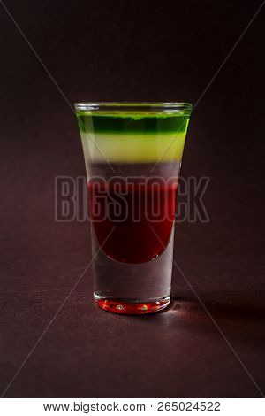 Alcoholic shot glass with grenadine, absent on elegant dark brown background. poster