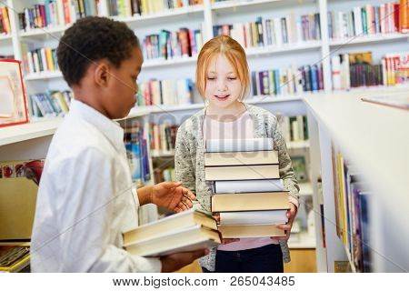 Two students in the library of the school with many books to study