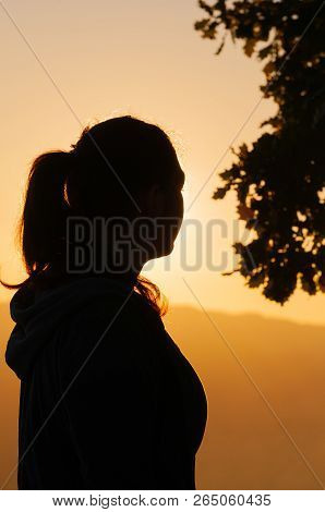 Silhouette Of A Young Female Hiker Watching The Sun Setting Over Hills In The Autumn