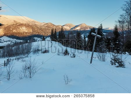 Sunrise Morning Winter Mountain Village Outskirts. View From Rural Snow Covered Path On Hill Slope W