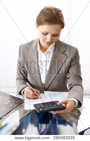 Bookkeeper woman or financial inspector  making report, calculating or checking balance. Business portrait. Copy space area for audit or tax concepts poster