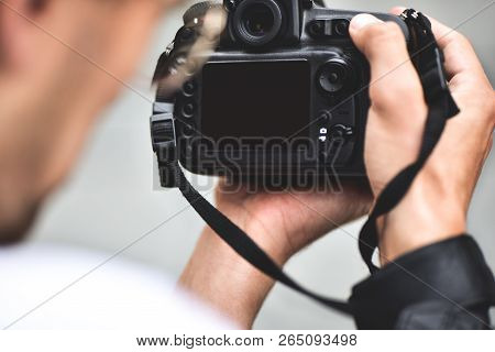 Digital Single-lens Reflex Camera In Hands. Photographer Shooting Hands Close Up. Man Photographer M