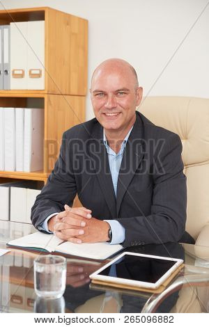 Portrait Of Balded Psychologist Specialist Sitting At The Table With Notepad And Touchpad And Smilin