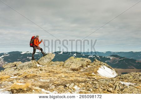 Climber With A Backpack On Top. A Man Went Up On The Mountain, People Traveling Through The Beautifu