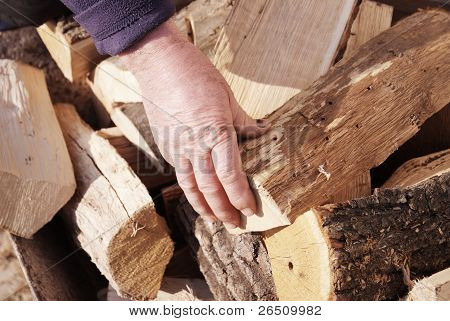 hand of worker on a stack of wood