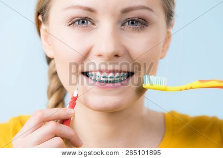 Dentist And Orthodontist Concept. Young Woman Smiling Cleaning And Brushing Teeth With Braces Using