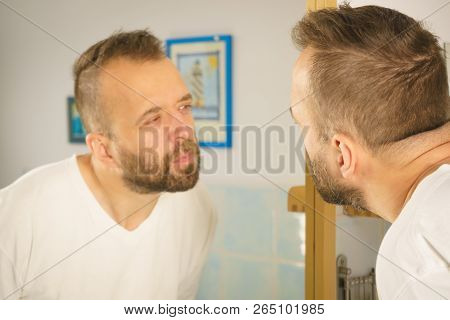 Adult Man Looking At Himself In Bathroom Mirror. Guy About To Do His Morning Hygiene Routine.