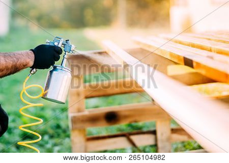 Close-up Of Industrial Worker Using Paint Gun Or Spray Gun For Applying Paint On Brown Timber Wood