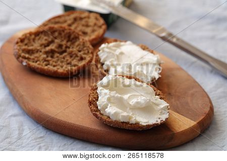 Sandwiches with cream cheese on a wooden cutting board