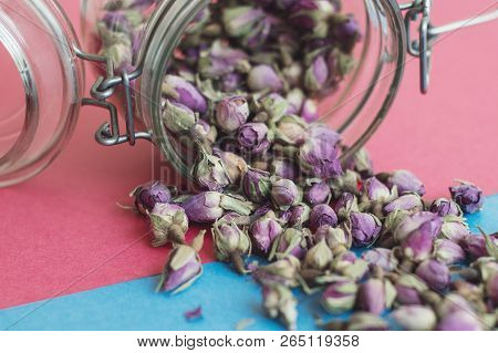 Rose Bud Tea And Glass Jar On Pink And Blue Background. Dried Herbal Tea