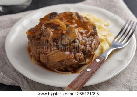 Salisbury steak with pasta under tomato and mushroom gravy