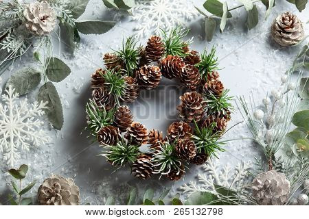 Christmas and New Year holidays concept with snowy fir branches and pine cone wreath on light background. Christmas greeting card, top view.
