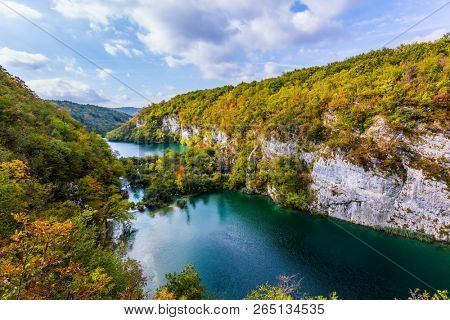 Plitvice cascading lakes with emerald water among the low hills. Autumn trip to Croatia. The concept of ecological and active tourism