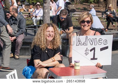 New York, Usa - April 14, 2018: Advice For 1 Us Dollar. Women In The Park Giving Payed Advices In Th