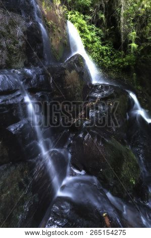 Landscape Of A Small Waterfall Cascading Over A Rock With A Long Exposure