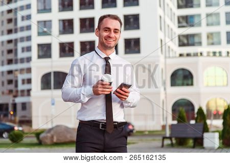 Happy Smiling Businessman Using Modern Smartphone Near Office At Early Morning