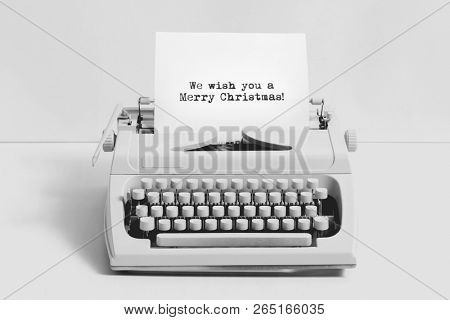Christmas wishes written on an old typewriter on white background. Minimalistic Christmas concept.