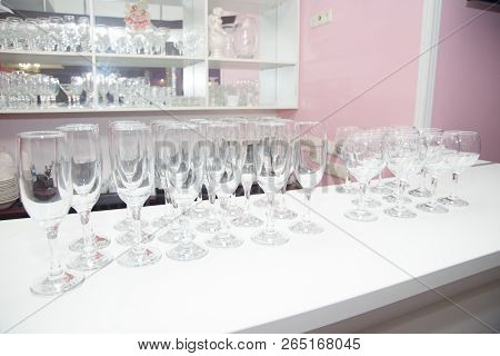 Crystal Clear Empty Wine Glasses On The Table. Alcohol Background. A Lot Of Wine Glasses At The Bar