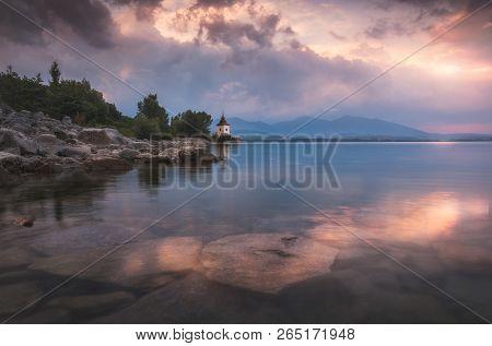 Church By Liptovska Mara Lake With Western Tatras Mountains In Background At Sunset In Slovakia