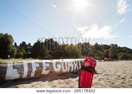 A Lifeguard Buoy In The Sand In Front Of A Log With Lifeguard Written On It.