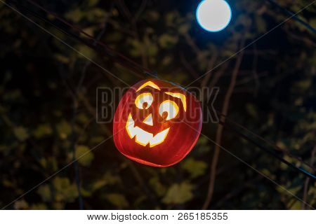 Glowing Pumpkin Hanging On Wire At Night For Halloween