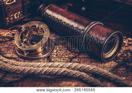 Travel geography navigation concept still life background - old vintage retro compass with sundial, spyglass and rope on ancient world map poster