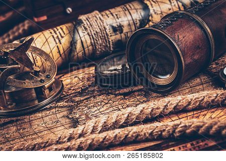 Travel geography navigation concept still life background - old vintage retro compass with sundial, spyglass and rope on ancient world map
