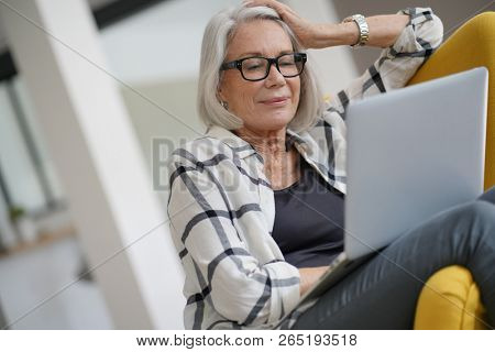 Relaxed modern senior woman at home on computer