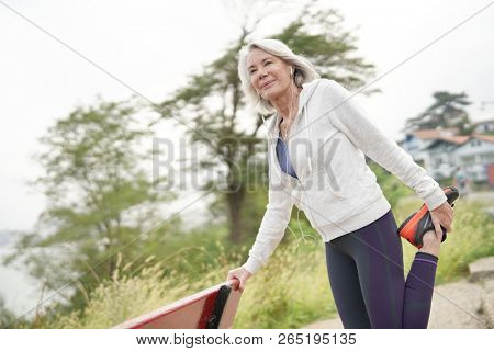 Senior woman stretching outdoors before running