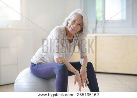 Lovely senior woman sitting on swiss ball between exercises