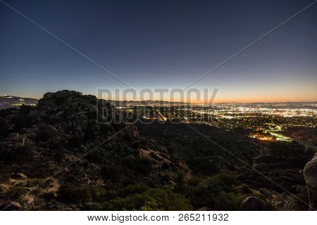 Los Angeles California predawn rocky hilltop view of the San Fernando Valley.  Burbank, North Hollywood, Griffith Park and the San Gabriel Mountains are in background.
