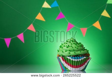 Festive Cupcake With Cream On A Green Background Decorated With Colorful Garland