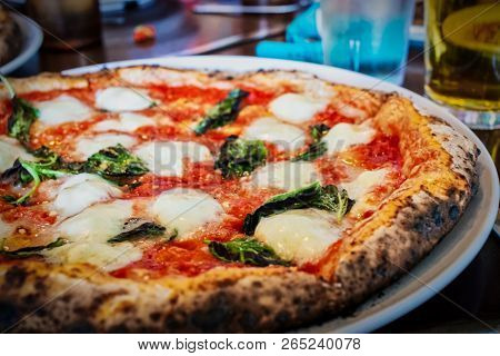 An Italian Pizza Margherita With Drinks Sitting On A Table.