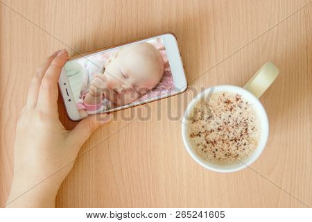 View Handheld Color Video Baby Monitor. Female Hands Are Holding A Smartphone With A Baby Monitor Ap