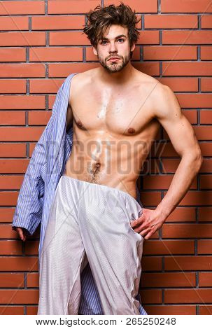 Guy shimmering skin undressing bathrobe. Sportsman show six pack sexy torso. Bachelor sexy body chest and belly. Sexy attractive macho tousled hair on wooden background. Man athlete with fit torso poster
