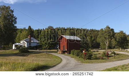 Medelpad, Sweden On 05. View Of Some Buildings, Driveways Signs And A Forest In The Background On Ju