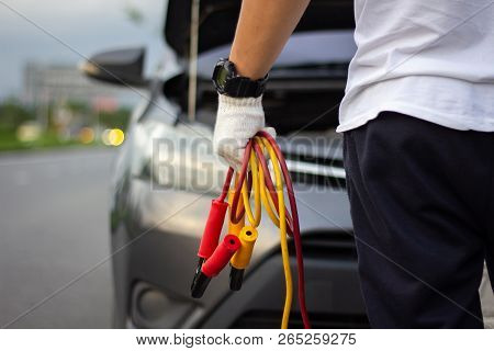 Car Mechanic Man Holding Battery Jumper Cables To Charge A Dead Battery. Close Up Hand Charging Car