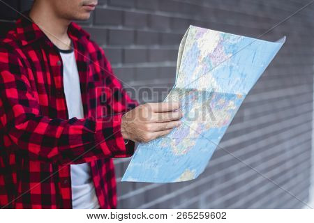 Young Man Looking In Open Map. Traveler Standing With Road Map In Hands.