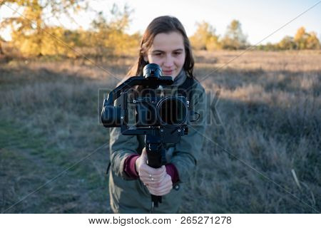 Female Videographer Holding A Gimbal With Mirrorless Camera. Woman With Stabilized Camera Rig Filmin