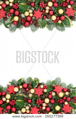 Christmas background border with red and gold bauble decorations, holly berries, spruce pine, ivy, pine cones and mistletoe on white.