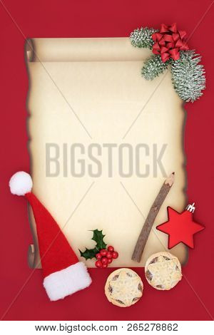 Letter to Father Christmas or invitation with blank parchment paper, santa hat, mince pies, pencil, bow, star bauble and winter flora on red background. Christmas Eve concept.