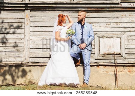 Just Married Loving Hipster Couple In Wedding Dress And Suit Posing In Front Of An Old Wooden House.