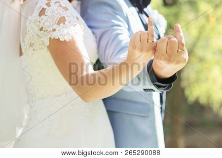 Couple Showing Middle Fingers With Wedding Rings