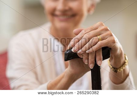 Closeup of senior woman hands holding black walking stick while sitting on couch. Hands of elderly woman holding cane. Old age concept.