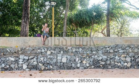 Woman Sitting On Wall At Beach Looking Into Hand Mirror
