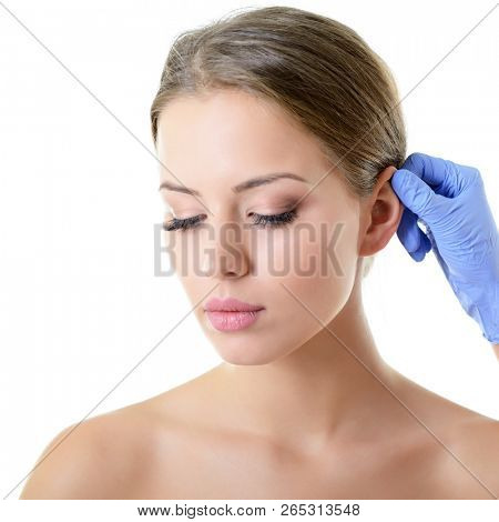Young beautiful female face, doctor's hand in gloves touchs ear of woman, isolated on white. Beauty treatment, lifting, skincare, plastic surgery concept.