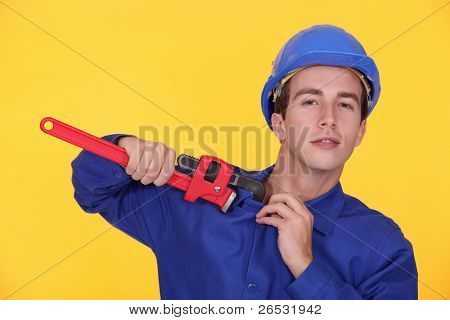 portrait of young plumber holding adjustable spanner against yellow background poster