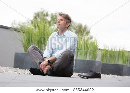 Senior business man with shoes off and legs cross performing meditation outdoors. He could be doing this to relax and make himself more comfortable when working on on a break or after finishing
