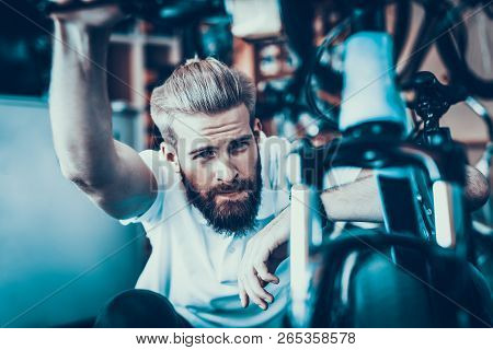 Man Looks At Cycle Details In Bike Workshop. Closeup Portrait Of Young Bearded Caucasian Man Wearing